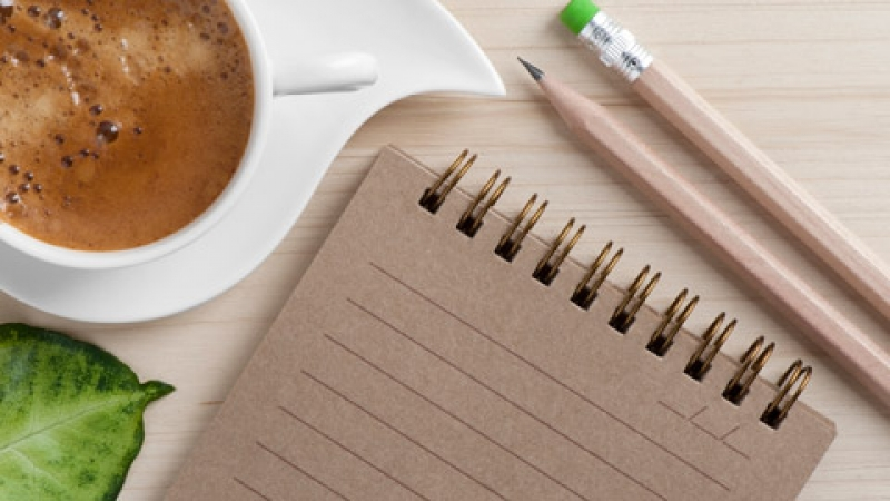 Coffee cup, notepad and pencils